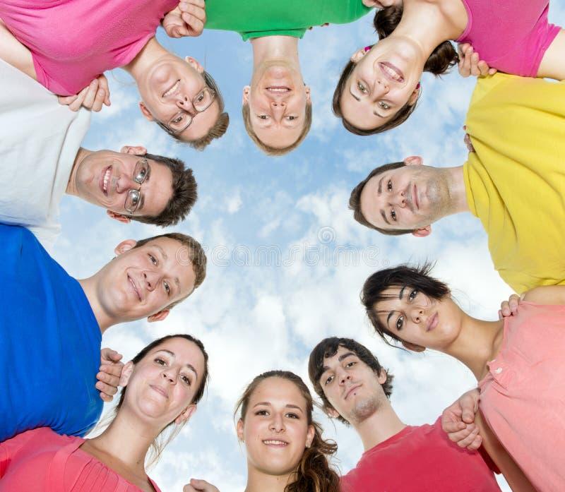 Glückliche Freunde, die einen Kreis bilden lizenzfreies stockfoto