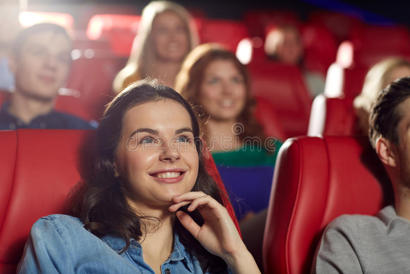 Glückliche Freunde, die Film im Theater aufpassen lizenzfreie stockbilder