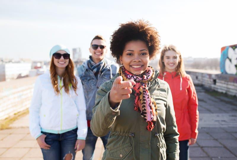 Glückliche Freunde, die Finger auf Sie auf Straße zeigen lizenzfreie stockbilder