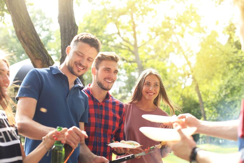 Glückliche Freunde, die Fleisch grillen und draußen Grillpartei genießen lizenzfreies stockfoto