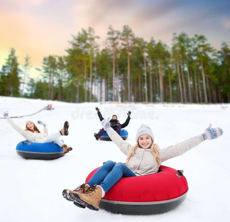 Glückliche Freunde, die hinunter Hügel auf Schneerohren schieben lizenzfreie stockbilder