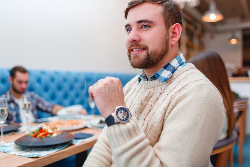 Glückliche Freunde, die im guten Restaurant zu Abend essen stockfoto