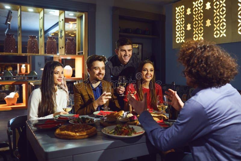 Glückliche Freunde, die im Restaurant zu Abend essen lizenzfreie stockfotos