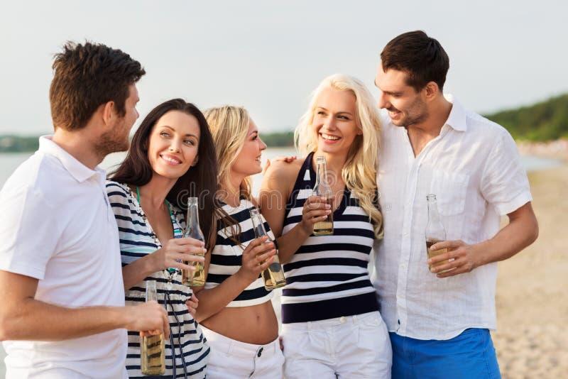 Glückliche Freunde, die nicht alkoholisches Bier auf Strand trinken lizenzfreies stockbild