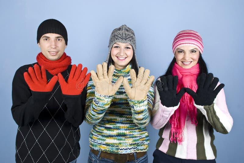 Glückliche Freunde, die Palmen in den Handschuhen zeigen stockfoto
