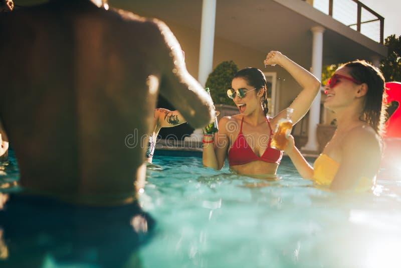 Glückliche Freunde, die Partei innerhalb des Pools machen lizenzfreies stockbild