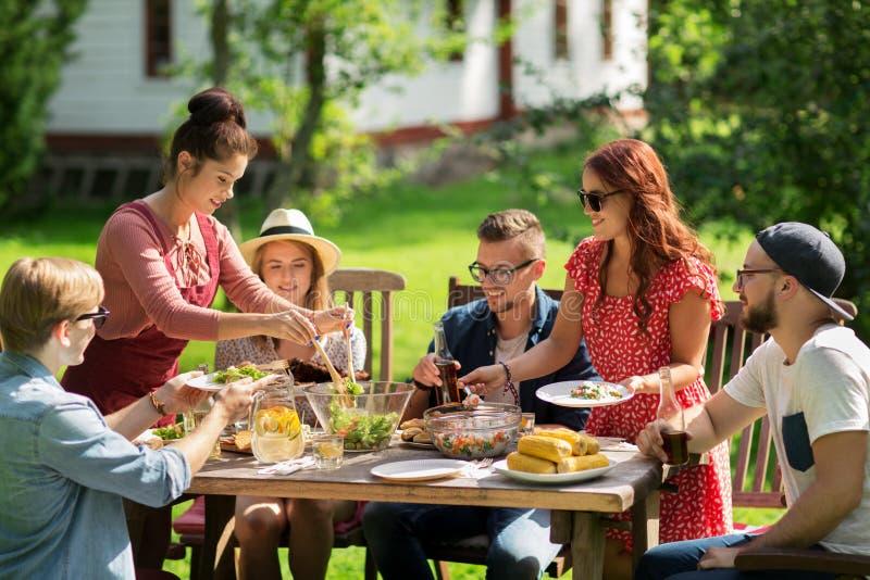Glückliche Freunde, die am Sommergartenfest zu Abend essen stockfotos