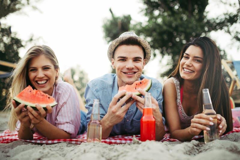 Glückliche Freunde, die Spaß auf dem Strand haben und Wassermelone essen lizenzfreie stockfotografie