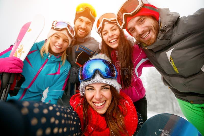 Glückliche Freunde, die Spaß auf Winter hodays haben Snowbarders und Skifahrer stockfotos