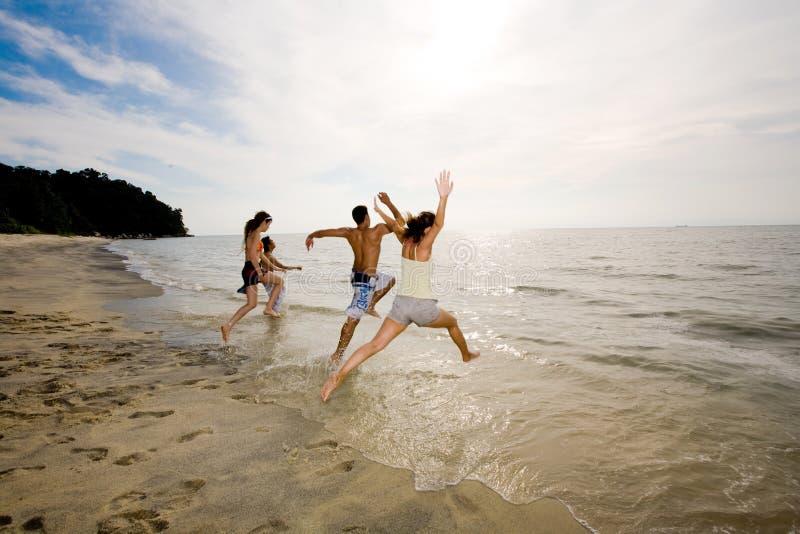 Glückliche Freunde, die Spaß durch den Strand haben lizenzfreies stockbild