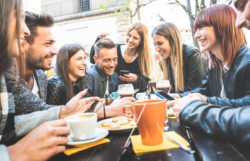 Glückliche Freunde, die Spaß mit intelligenten Mobiltelefonen sprechen und haben stockbild