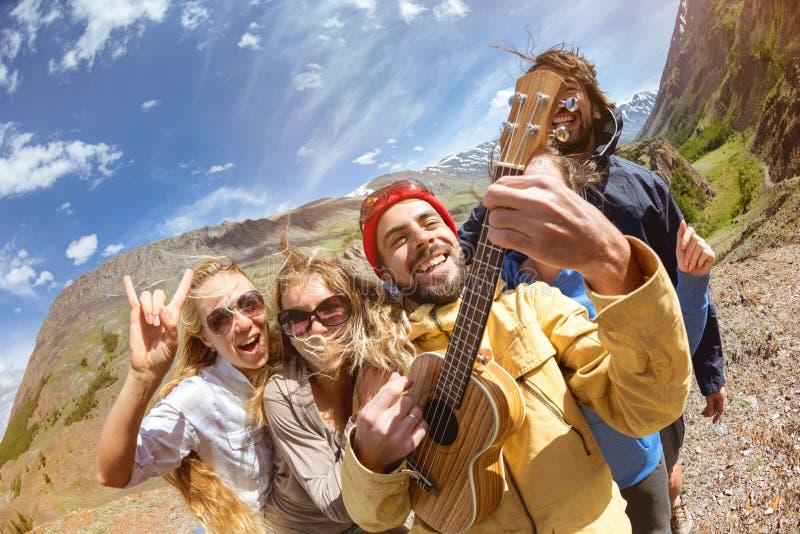 Glückliche Freunde, die Spaßspielgitarre draußen haben stockfotos