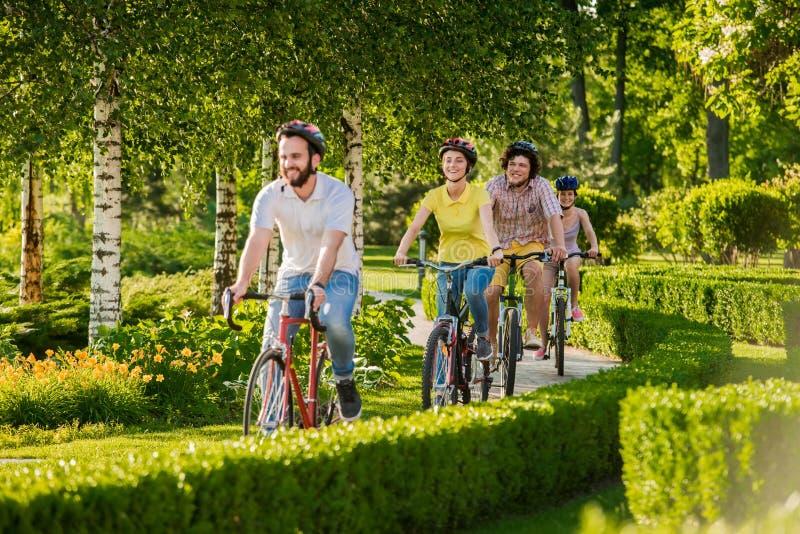 Glückliche Freunde, die in Stadtpark radfahren lizenzfreies stockbild