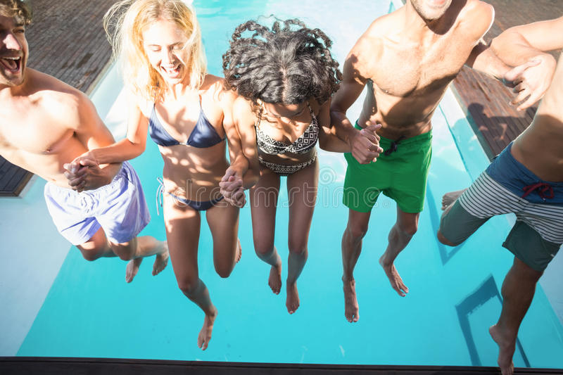 Glückliche Freunde, die am Swimmingpool genießen stockfotografie