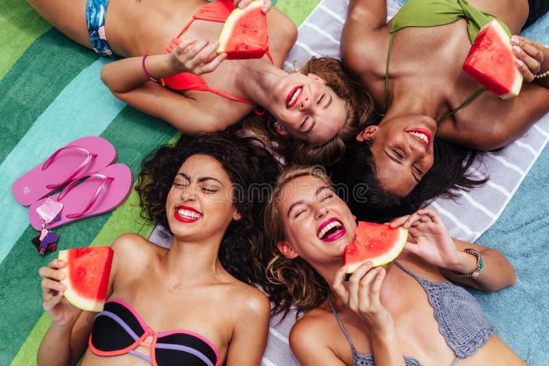 Glückliche Freunde, die Wassermelone durch den Poolside essen lizenzfreies stockbild