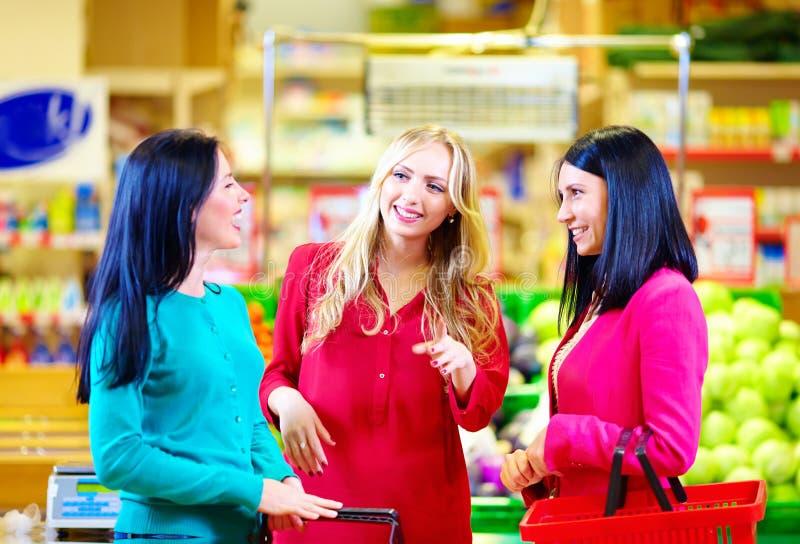 Glückliche Freunde, die zusammen im Lebensmittelgeschäftsupermarkt kaufen lizenzfreie stockfotografie
