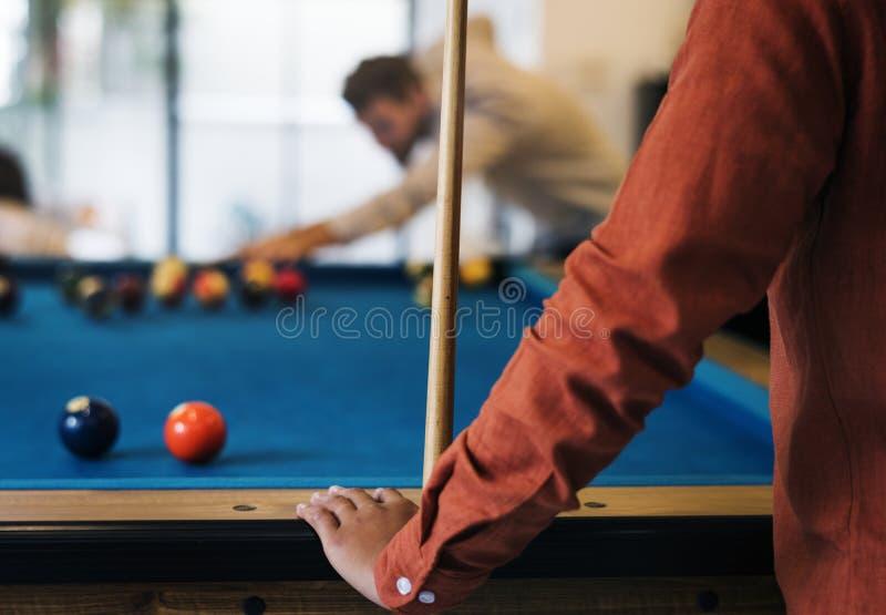 Glückliche Freunde, die zusammen Pool spielen stockfotografie
