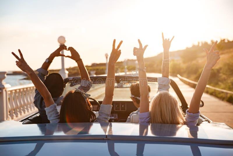 Glückliche Freunde im Cabriolet mit den angehobenen Händen, die auf Sonnenuntergang fahren stockfotos