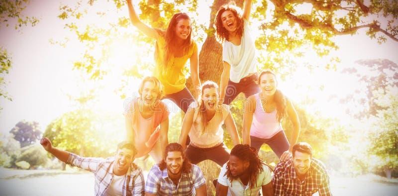 Glückliche Freunde im Park, der menschliche Pyramide macht lizenzfreies stockbild