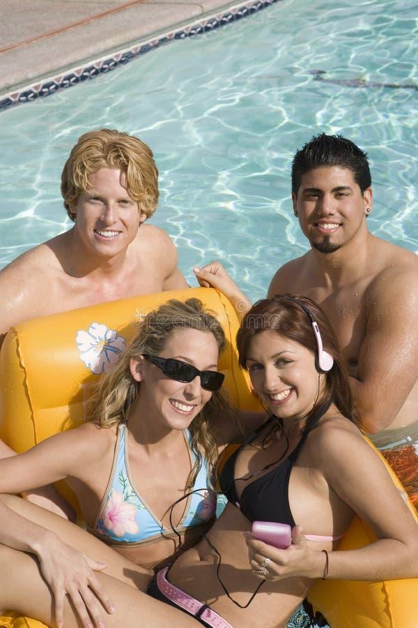 Glückliche Freunde im Pool lizenzfreie stockbilder