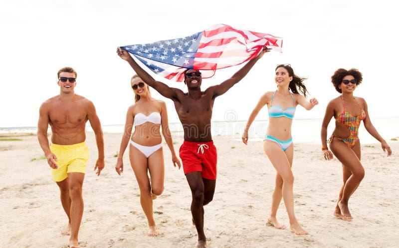 Glückliche Freunde mit amerikanischer Flagge auf Sommerstrand lizenzfreie stockfotos