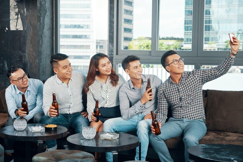 Glückliche Freunde mit dem Bier, das selfie nimmt stockfotografie