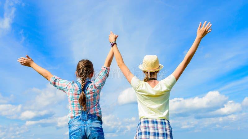 Glückliche Freunde mit den offenen Armen unter blauem Himmel lizenzfreie stockfotografie
