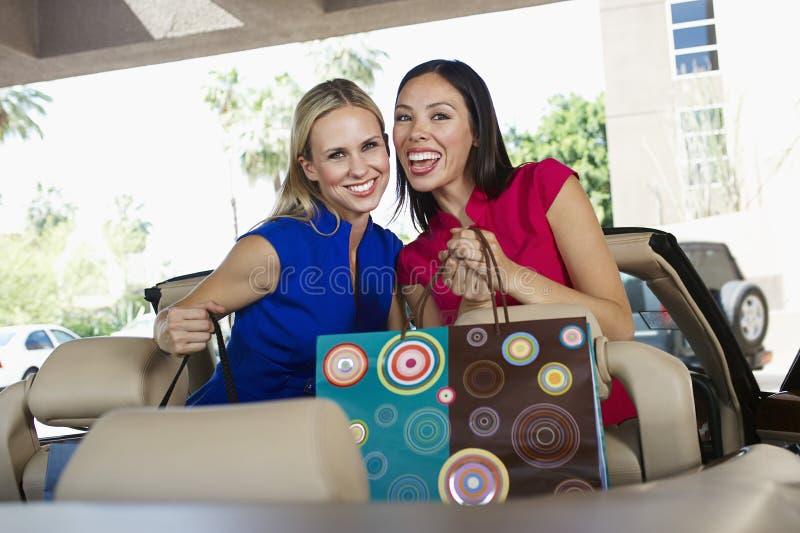 Glückliche Freunde mit Einkaufstaschen stockfotos