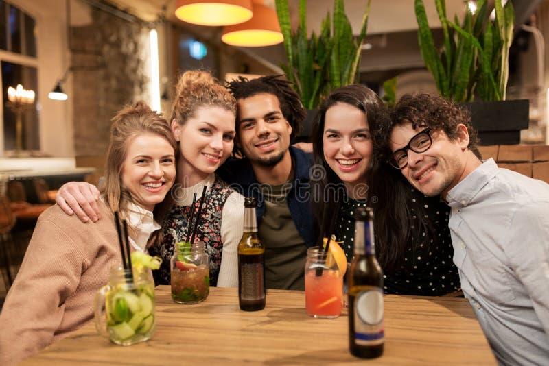 Glückliche Freunde mit Getränken an der Bar oder am Café stockbilder