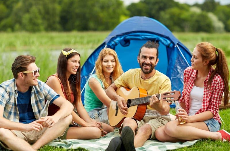 Glückliche Freunde mit Getränken und Gitarre am Kampieren lizenzfreies stockbild