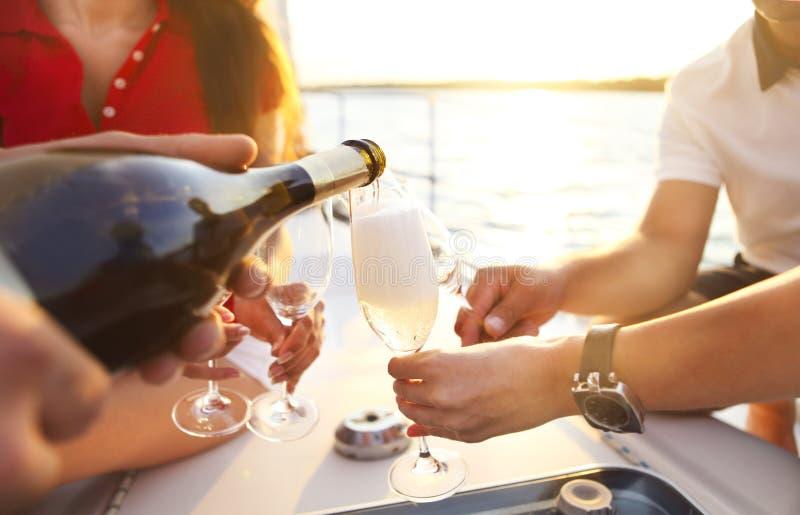 Glückliche Freunde mit Gläsern Champagner auf Yacht lizenzfreie stockfotos