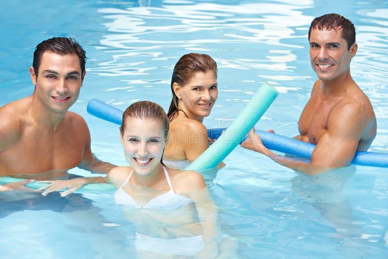 Glückliche Freunde mit Swimnudeln im Pool lizenzfreie stockfotos