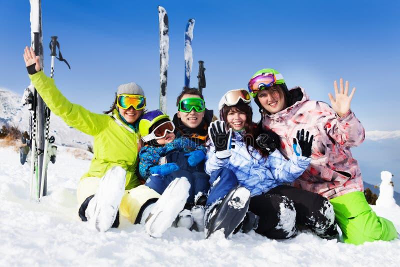 Glückliche Freunde, nachdem Sie sitzen Sie auf Schneewellenhänden Ski gefahren haben lizenzfreies stockbild