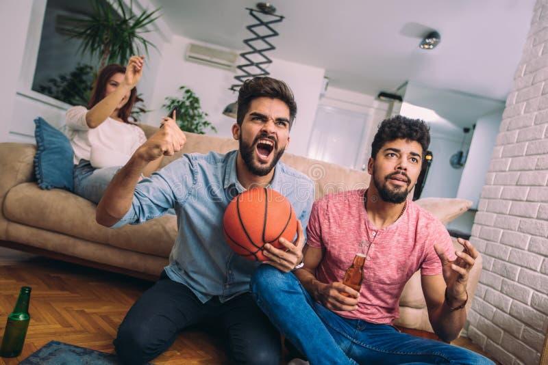 Glückliche Freunde oder Basketballfans, die Basketballspiel im Fernsehen aufpassen lizenzfreie stockfotos