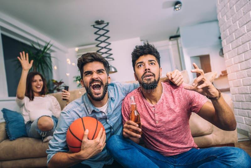Glückliche Freunde oder Basketballfans, die Basketballspiel im Fernsehen aufpassen lizenzfreies stockfoto