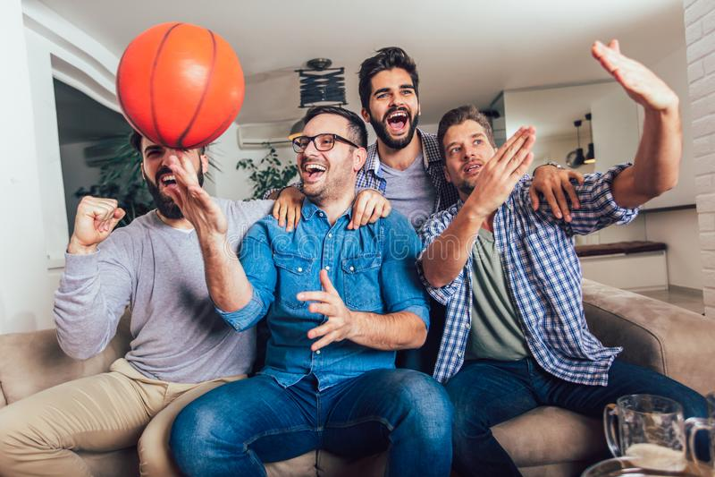 Glückliche Freunde oder Basketballfans, die Basketballspiel im Fernsehen aufpassen und zu Hause Sieg feiern stockbild