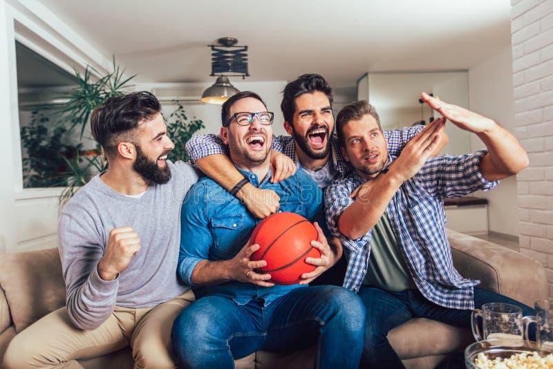 Glückliche Freunde oder Basketballfans, die Basketballspiel im Fernsehen aufpassen und zu Hause Sieg feiern lizenzfreies stockbild