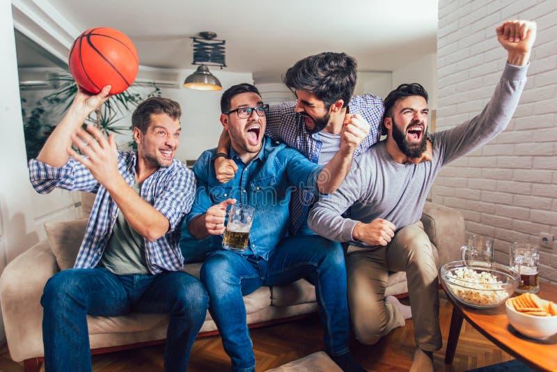 Glückliche Freunde oder Basketballfans, die Basketballspiel im Fernsehen aufpassen und zu Hause Sieg feiern lizenzfreie stockfotografie