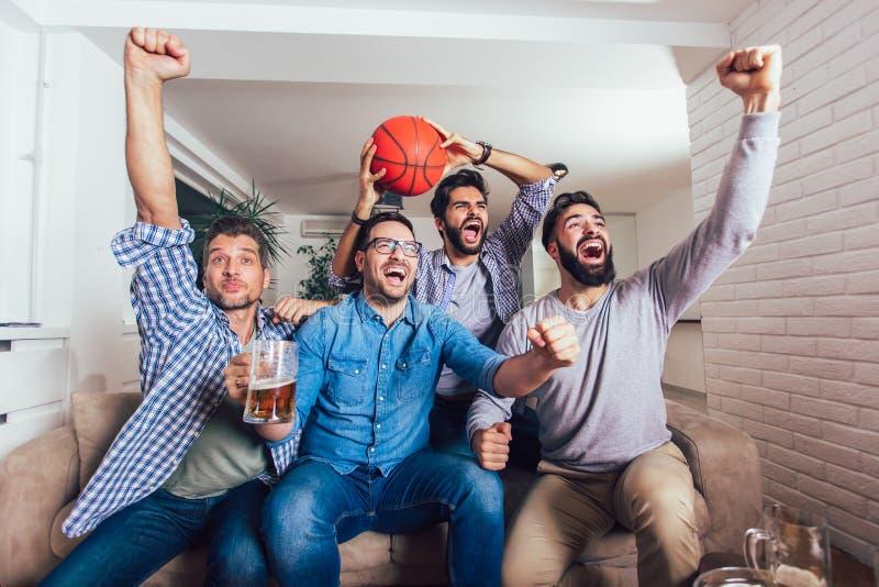Glückliche Freunde oder Basketballfans, die Basketballspiel im Fernsehen aufpassen und zu Hause Sieg feiern lizenzfreie stockfotos