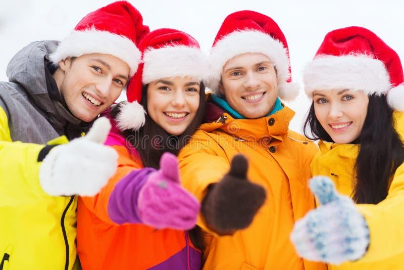 Glückliche Freunde in Sankt-Hüten und in den Skianzügen draußen lizenzfreie stockfotografie