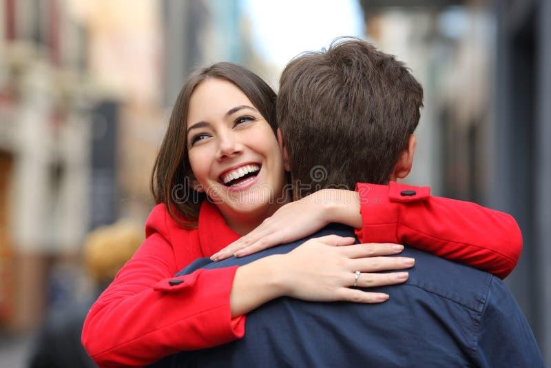 Glückliche Freundin, die ihren Freund nach Antrag umarmt stockbild