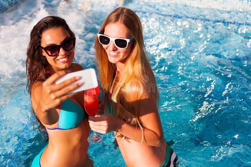Glückliche Freundin mit einem Getränk auf einem Sommerfest durch das Poolnehmen lizenzfreie stockfotografie