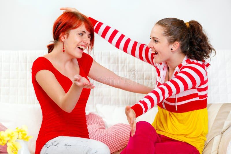Glückliche Freundinnen, die auf Sofa und der Umfassung sitzen lizenzfreies stockfoto