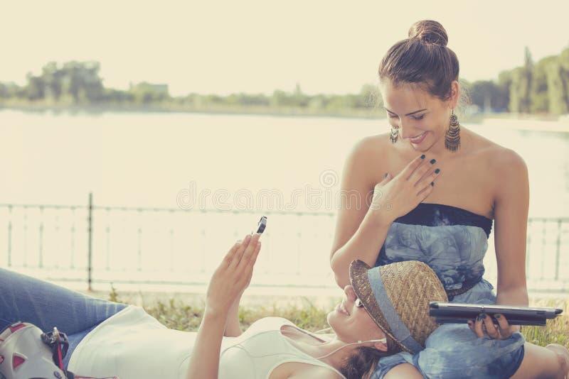 Glückliche Freundinnen, die Grasensocial media auf tragbaren Geräten lachen stockbild