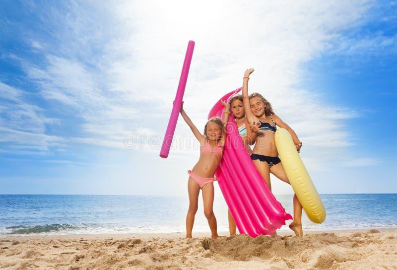 Glückliche Freundinnen, die Spaß auf sandigem Strand haben stockbilder