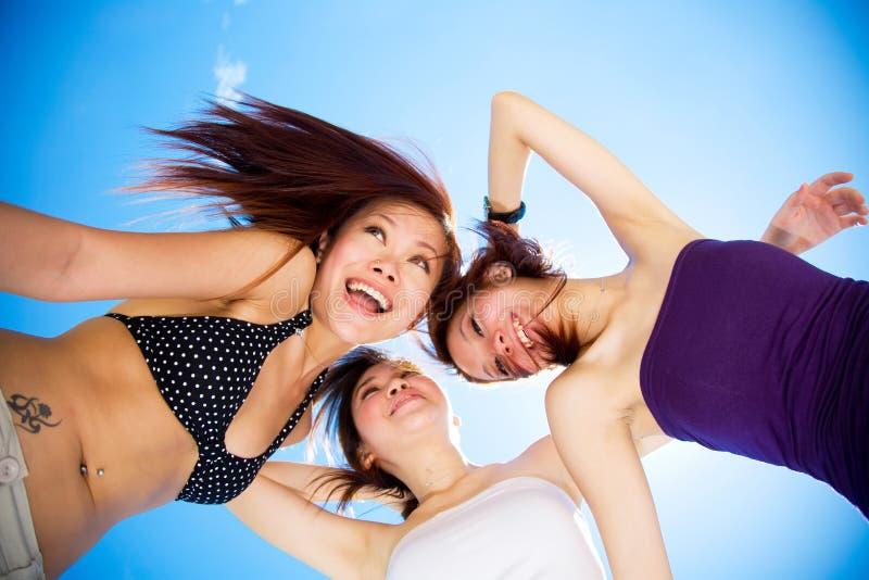 Glückliche Freundinnen, die Spaß unter hellem blauem Himmel haben stockfoto