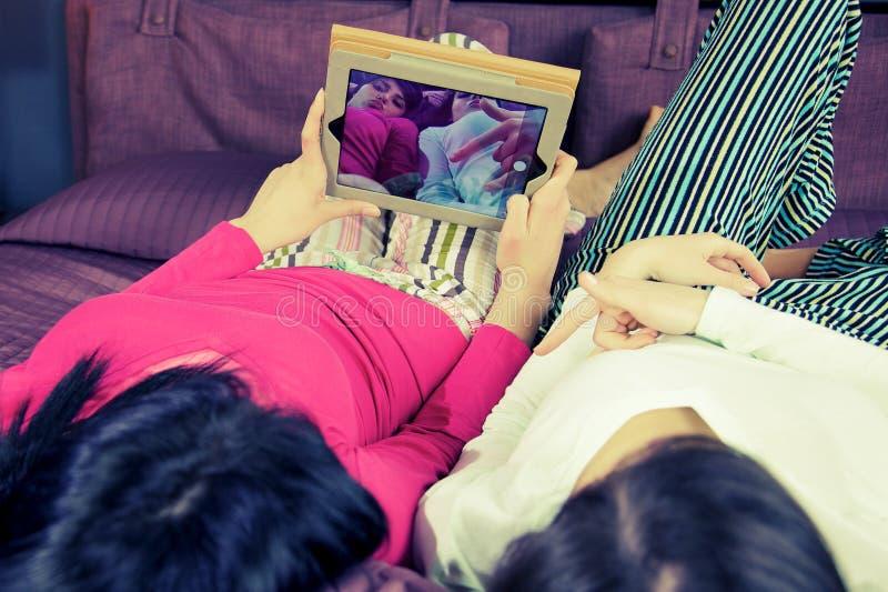 Glückliche Freundinnen im Bett, das selfie mit der Tablette lustig nimmt lizenzfreies stockbild