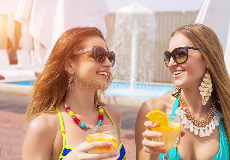 Glückliche Freundinnen mit Getränken nahe dem Pool lizenzfreie stockfotos