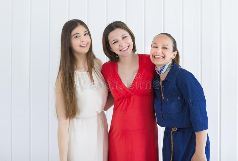 Glückliche Freundinnen mit schwangerer Frau lizenzfreie stockbilder