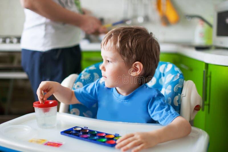 Glückliche freundliche Kindzeichnung mit Pinsel im Album unter Verwendung vieler Anstrichhilfsmittel Hand, die lego Wand aufbaut lizenzfreies stockfoto